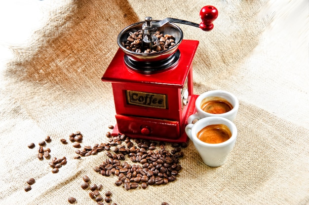 Picture of red vintage coffee grinder with two coffee cups Premium Photo
