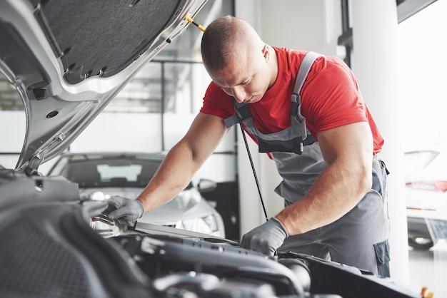 Immagine che mostra il lavoratore di servizio auto muscolare che ripara veicolo. Foto Gratuite