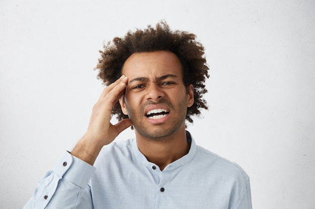 Picture of stressed young employee in formal shirt having headache Free Photo