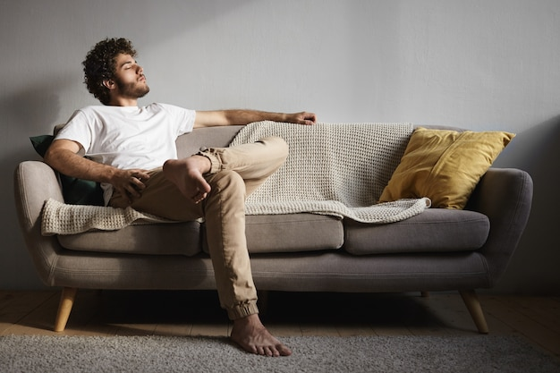Picture of stylish handsome young guy with fuzzy beard, voluminous hairdo and bare feet keeping eyes closed, falling asleep or listening to classical music, enjoying leisure time, sitting on couch Free Photo