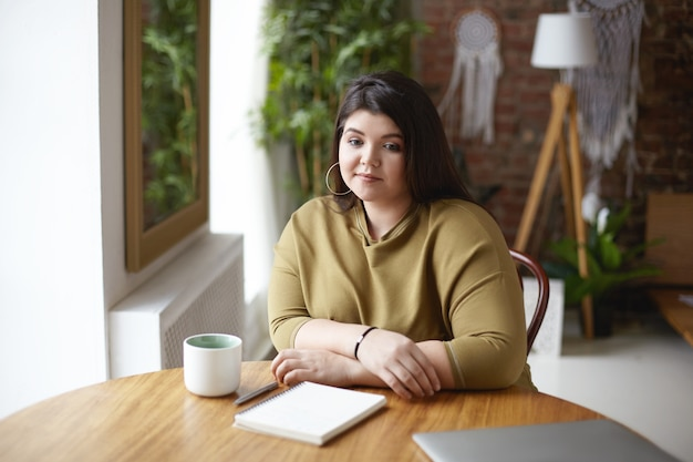 Foto di elegante designer femminile giovane sovrappeso seduto al posto di coworking e bere caffè, pensando al concetto di nuovo progetto, abbozzando nel diario, avendo uno sguardo pensieroso pensieroso Foto Gratuite