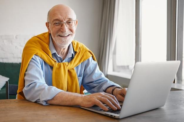Immagine di successo positivo anziano barbuto blogger di viaggio europeo che scrive un articolo sul computer portatile, guardando e sorridendo che indossa un maglione elegante intorno al collo sopra la maglietta blu Foto Gratuite
