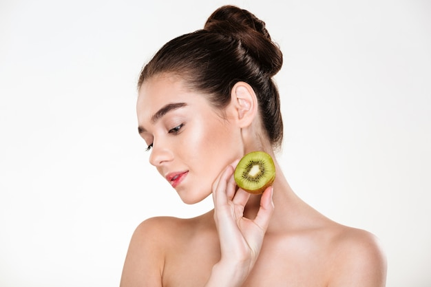 Picture of tender woman having clean skin posing with closed eyes holding ripe juicy kiwi in hand Free Photo