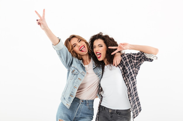 Picture of two playful girls standing together and showing peace gestures  over white wall Free Photo