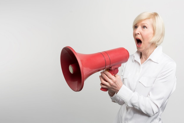 A picture of white-haired woman standing a pronouncing a speech for defencing human rights and support feminists. she is using a speaker for that purpose. Premium Photo