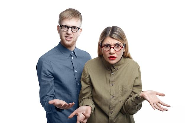Foto di giovane uomo barbuto e donna bionda entrambi con gli occhiali in piedi ed esprimendo indignazione, scrollando le spalle e facendo un gesto impotente perché non hanno idea di cosa stia succedendo Foto Gratuite