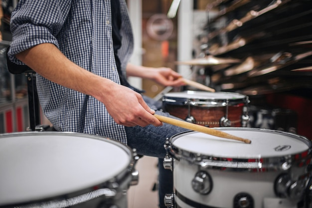 Picture of young bearded man playing on drus. he touches them with special sticks. many cymbals are above on shelfs. guy is alone in room. Premium Photo