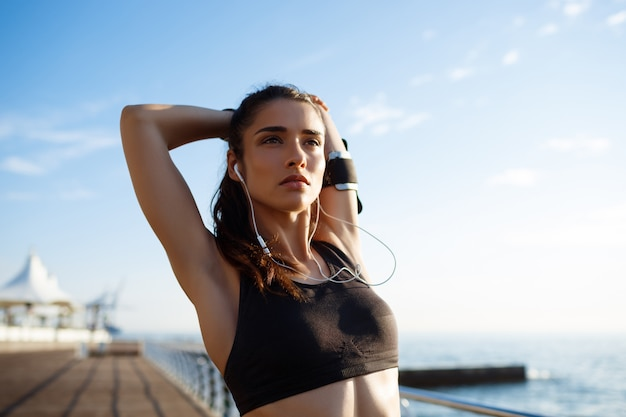 Picture of young beautiful fitness woman makes sport exercises with sea coast on wall Free Photo