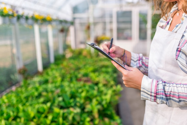 Picture of young woman standing in greenhouse holding clipboard. looking aside. Premium Photo