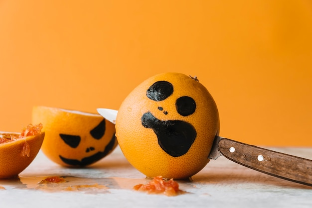 Pictured fruit with pierce knife and halloween orange behind Free Photo