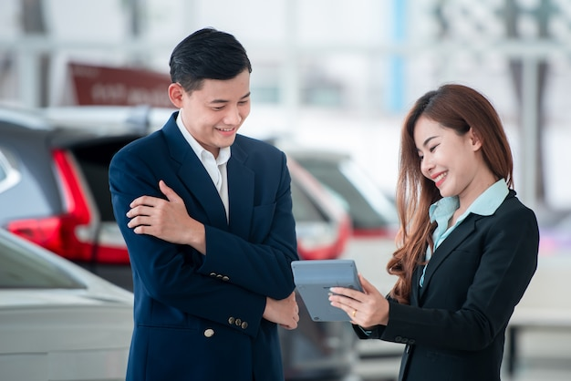 Pictures of asian customers and happy salespeople who buy new cars that enter into sales agreements with car dealers at car dealers. Premium Photo