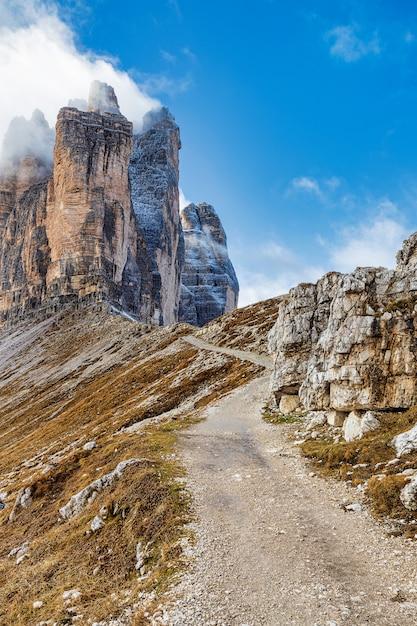 Живописная пешеходная тропа в доломитовых альпах с видом на знаменитые горы тре-чиме. Premium Фотографии