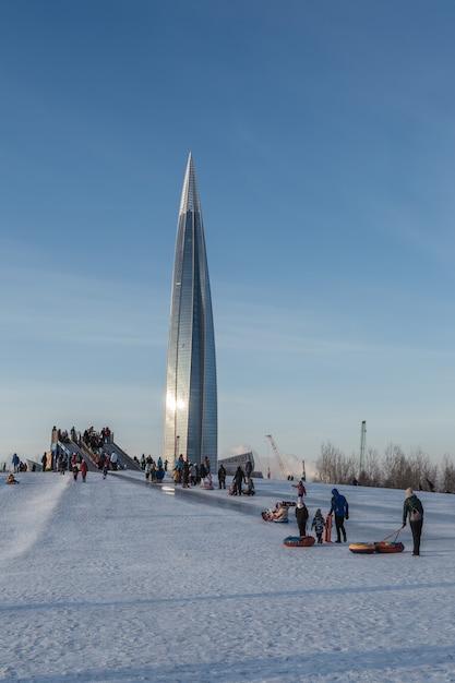 子供たちがいる絵のように美しい都会のシーンは、巨大な近代的な塔のそばでそりに行きます。 Premium写真