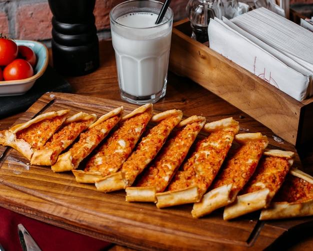 Вид сбоку турецкого pide с овощами и мясом на деревянной разделочной доске Бесплатные Фотографии
