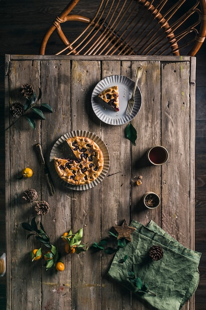 Pie with berries on a wooden table with a serving top view. Premium Photo