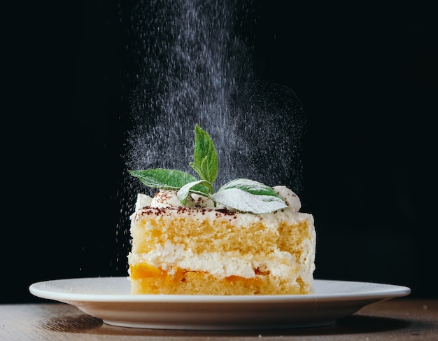 Piece of biscuit cake with white cream decorated with mint and powered sugar. Premium Photo