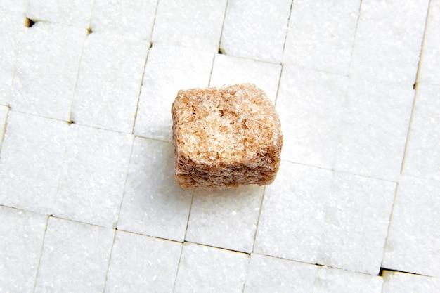 白い砂糖の立方体の上に置く茶色の砂糖を精製されていない砂糖 Premium写真