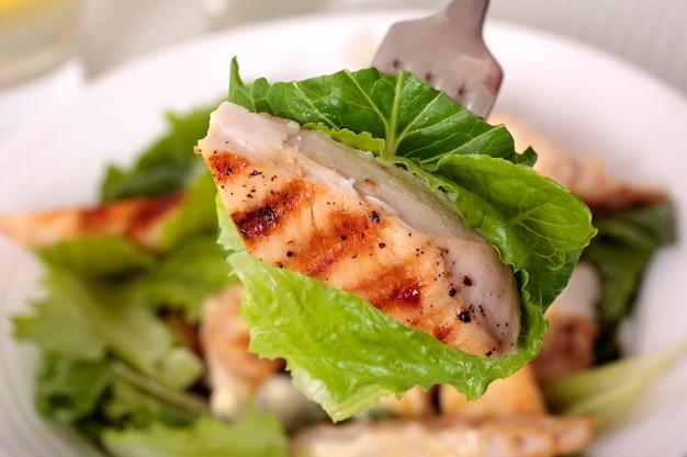 A piece of chicken caesar salad Free Photo