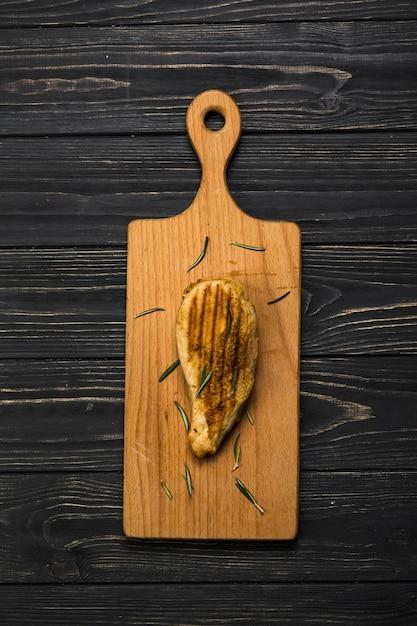 Pezzo di pollo sul tagliere Foto Gratuite