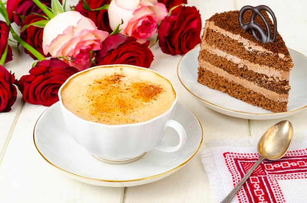 Piece of chocolate cake, cappuccino, flowers on table. Premium Photo