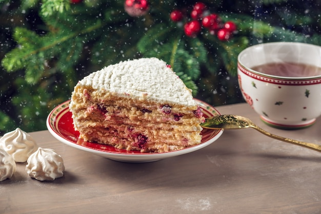 Piece cranberry cake covered with white cream on plate on the background of the christmas tree Premium Photo