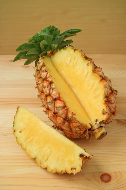 Piece of fresh ripe pineapple cut from the whole fruit isolated on wooden table Premium Photo