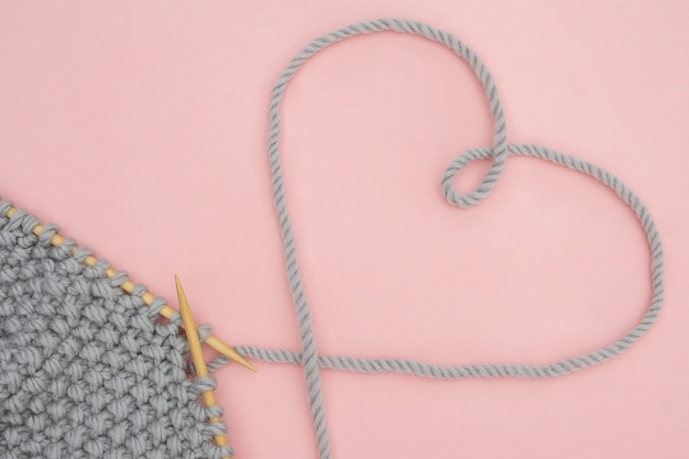 Piece of grey knitted fabric on wood needles and thread heart shape Premium Photo