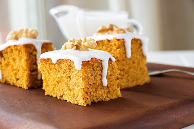 Piece of homemade carrot cake with nuts and icing cream. Premium Photo