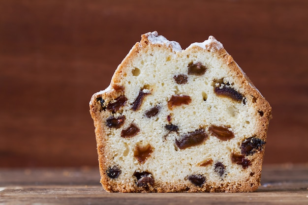 A piece of homemade traditional cupcake with raisins on the wooden background. Premium Photo