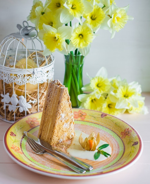 Piece of honey cake in a plate next to vase with daffodils Free Photo