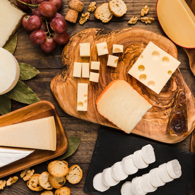 Piece of natural cheeses on cheese board with tasty ingredient over wooden desk Free Photo