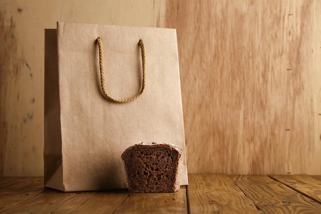 근처에 제시된 갈색 호밀 빵 조각 나무 배경에 장인 빵집에서 공예 종이에서 빈 가방을 빼앗아 무료 사진
