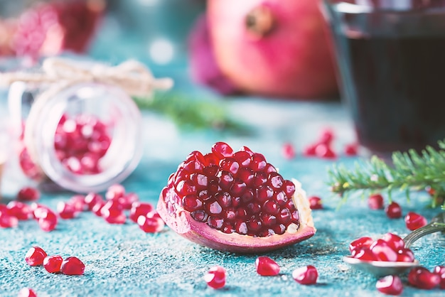 Piece of ripe pomegranate fruit with fir tree branches on blue vintage Premium Photo