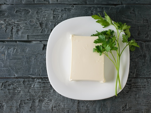 A piece of serbian cheese on a white bowl on a black wooden table. Premium Photo