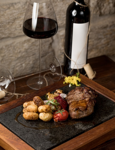A piece of steak with round grilled tomatoes and a glass of red wine Free Photo