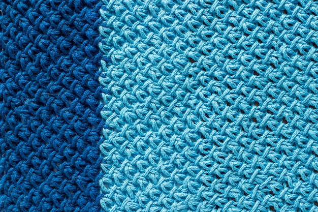 Piece of two-color blue knitted fabric, background or texture. knitting yarn handmade Premium Photo
