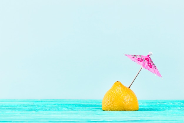 Piece of yellow lemon with pink umbrella on top on blue background Free Photo