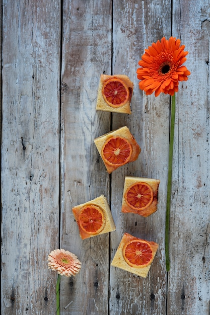 A pieces of blood orange cake and red flower on wooden background Premium Photo