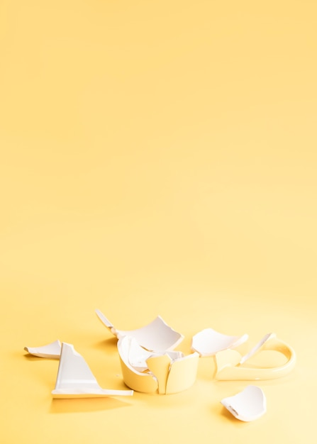 Pieces of a broken yellow mug Free Photo
