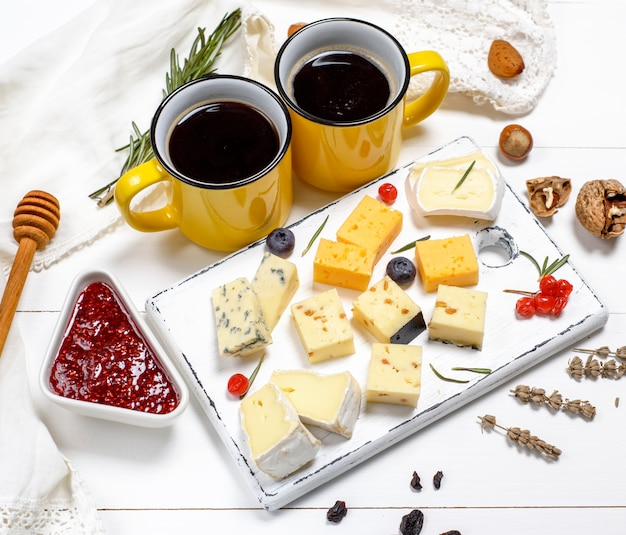Pieces of cheese on a white wooden board Premium Photo