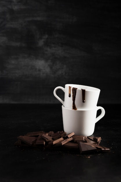 Pieces of chocolate and pile of mugs Free Photo