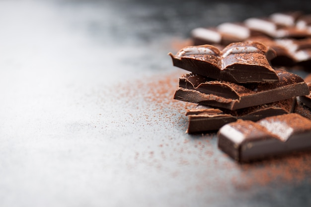 Pezzi di cioccolato su un tavolo in legno e cacao spruzzato Foto Gratuite