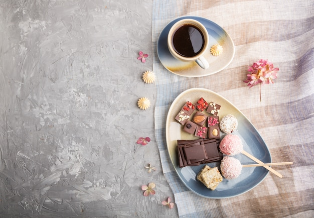 A pieces of homemade chocolate with coconut candies and a cup of coffee. top view Premium Photo