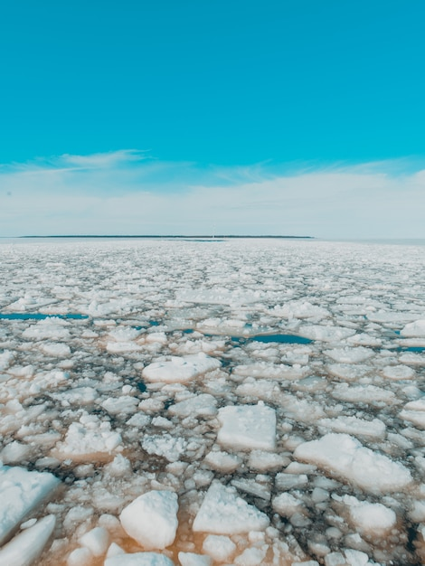Pieces of ice in the frozen lake under the bright sky in winter Free Photo