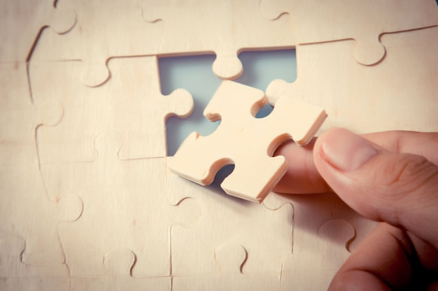 Pieces of jigsaw puzzle in woman's hands Premium Photo