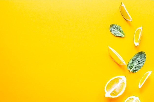 Pieces of lemon, lime and green mint leaves on a yellow background. Premium Photo