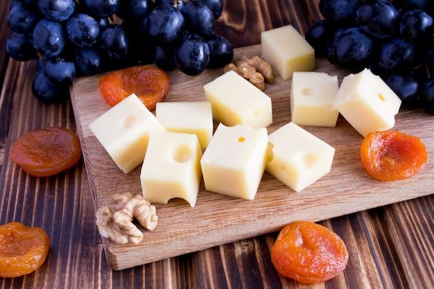 チーズ、ドライアプリコット、まな板の上の黒ブドウ Premium写真