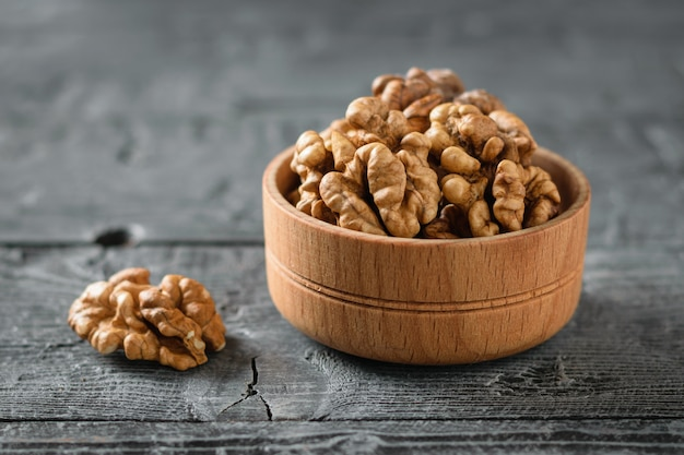 Pieces of peeled walnut in a wooden bowl on a dark wooden table. Premium Photo