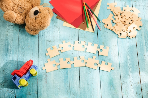 Pieces of puzzle, crayons, toy truck, teddy bear and paper on a wooden table. concept of childhood and education. Free Photo