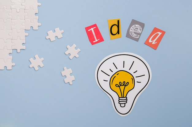 Pieces of puzzle and idea letters with light bulb Free Photo